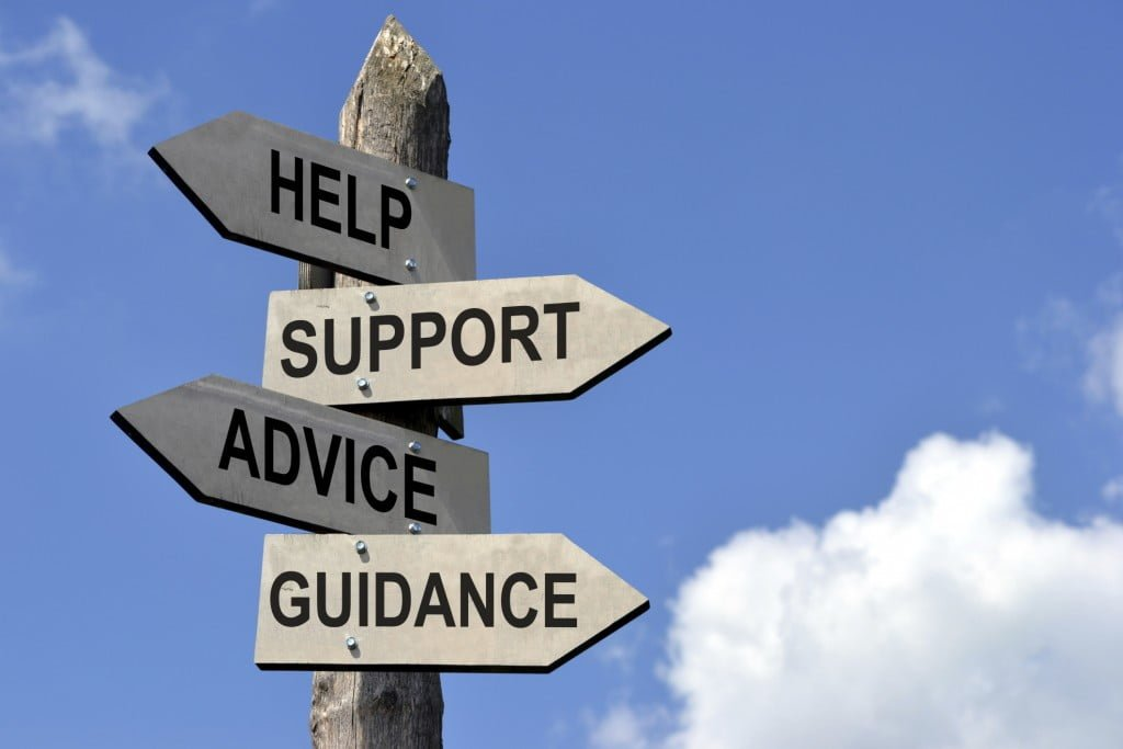 A wooden picket sign with signs for help, support, advice, and guidance