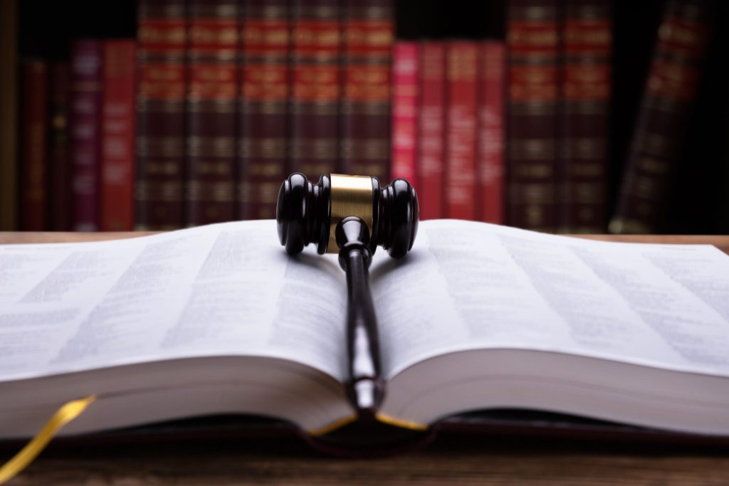 A book of law open with a gavel on top, and red books on a bookshelf behind.